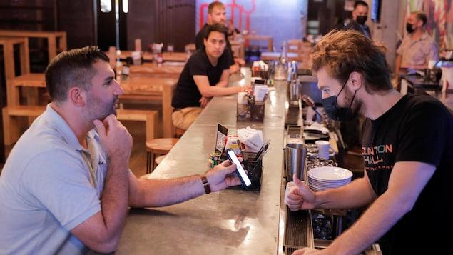 Un serveur derrière le bar regarde le téléphone que lui montre le client assis devant lui.