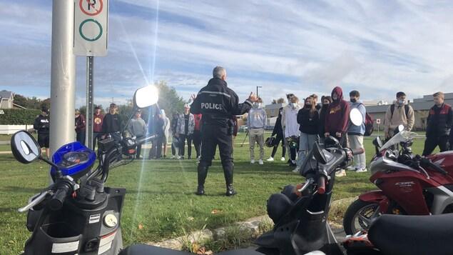 Un policier parle devant des jeunes.