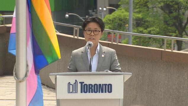 Une femme derrière un lutrin et un micro. Deux drapeaux sont à gauche, celui de la fierté gaie et transgenre.
