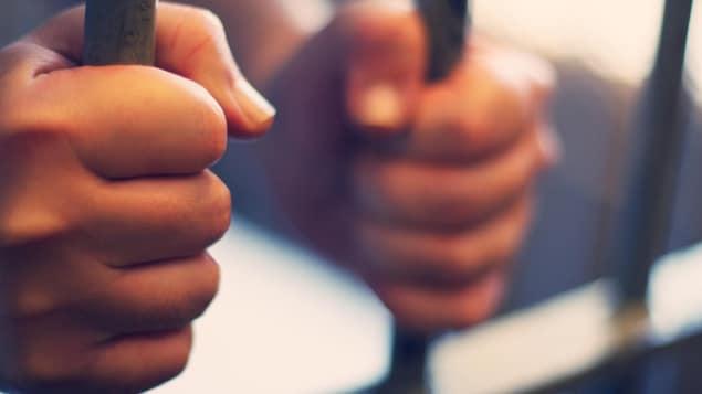 Un homme tient les barreaux d'une cellule de prison.