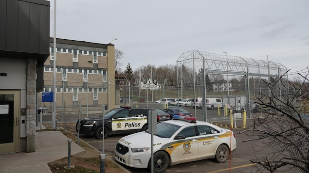 Des véhicules de la Sûreté du Québec sont garés devant le centre de détention de New Carlisle, entouré de clôtures munies de fils de fer barbelés.