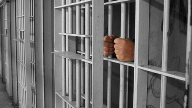 Des mains tiennent des barres dans une prison.