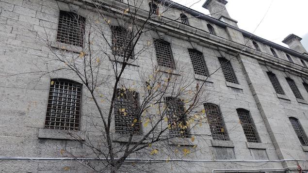 Un édifice de pierre gris sur lequel toutes les fenêtres ont des barreaux.