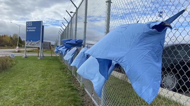 Des chemises accrochées à une clôture.