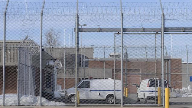 Des véhicules sont stationnés derrière les grilles de la prison.