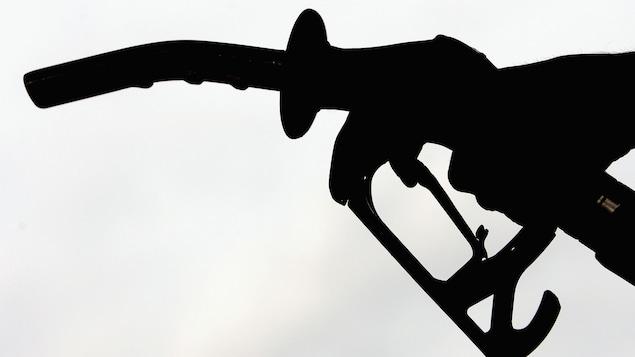 Une pompe à essence apparaît en contre-jour.