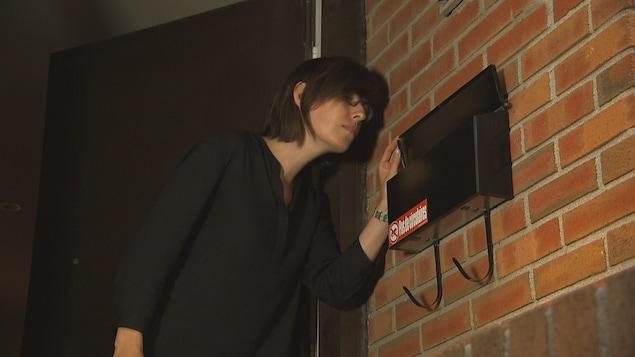 Une jeune femme vérifie s'il y a du courrier dans sa boîte aux lettres, mais celle-ci est vide.