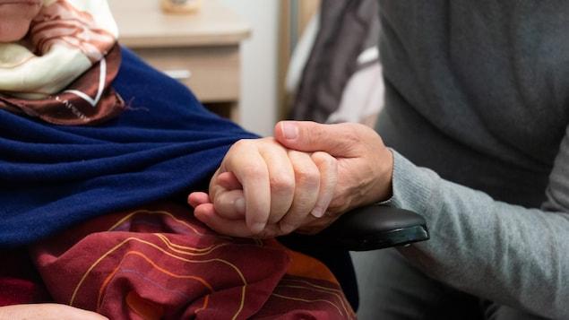 Un homme tient la main d'une femme en fauteuil roulant.