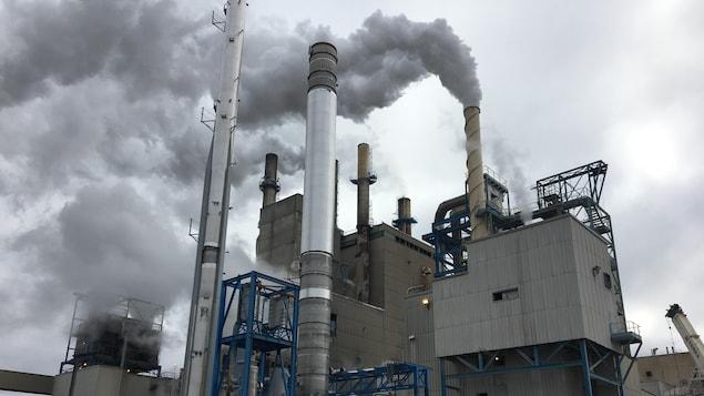 De grandes cheminées de l'usine évacuent de la fumée.