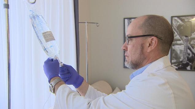 Un homme habillé d'un sarrau manipule une préparation médicamenteuse liquide.