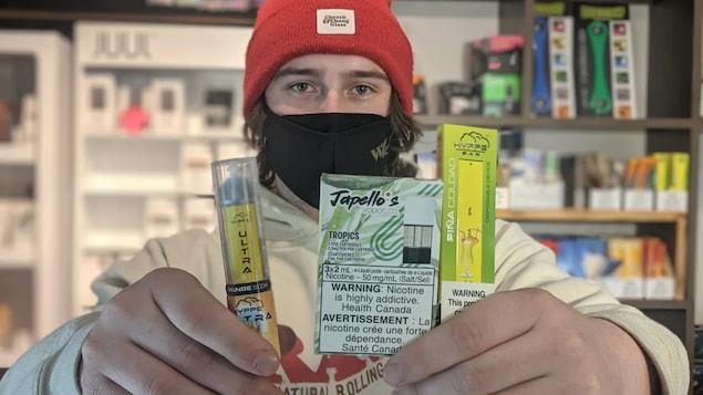 L'homme tient dans ses mains deux cigarettes électroniques et des cartouches aromatisées.