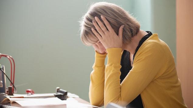 Une femme est assise à un bureau, la tête entre les mains.