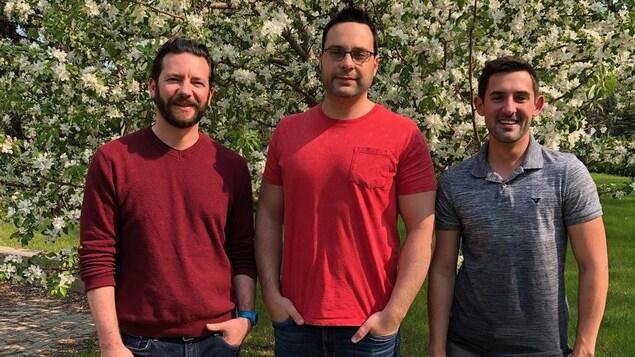Trois hommes se tiennent debout devant un arbre en fleur.