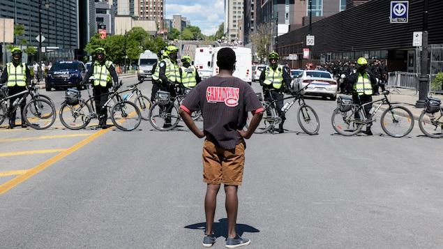 Un homme, les mains sur les hanches, se tient debout en étant tourné vers des policiers à bicyclette.