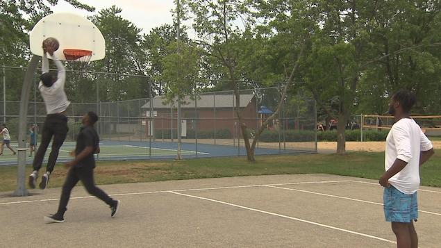 De jeunes Noirs jouent au basket.