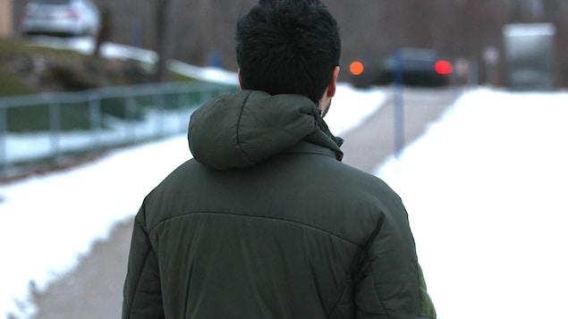 Un jeune homme photographié de façon anonyme pose de dos