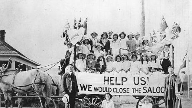 Groupe de femmes sur un chariot tiré par des chevaux et tenant une grande bannière.