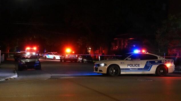 Des voitures de police et un périmètre de sécurité, érigé devant l'appartement de la victime.