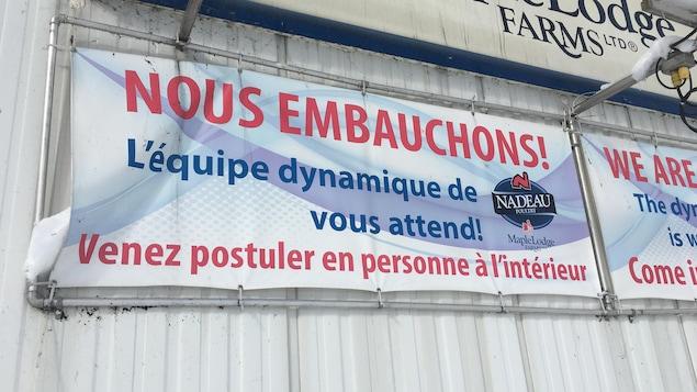 Une affiche indiquant une possibilité d'embauche chez Nadeau Ferme Avicole.