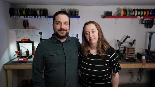 Un couple sourit dans leur atelier de travail.