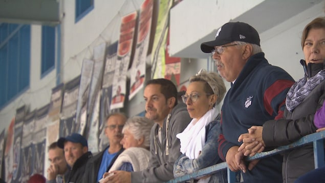 Des parents regardent leur enfant disputer un match de hockey.