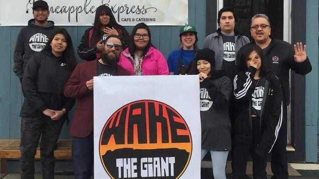 Un groupe de personnes tenant une grande affiche devant un café.