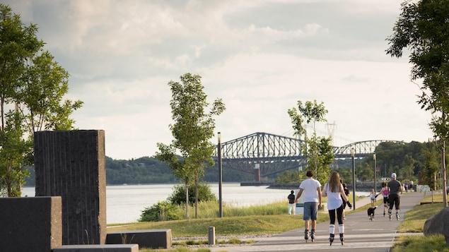 Des citoyens circulent en patins à roues alignées sir la promenade Samuel-De Champlain.