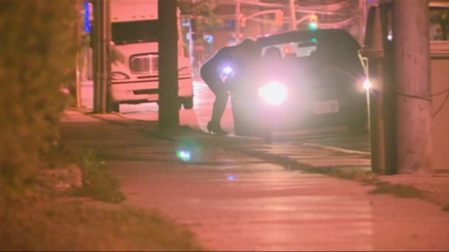 Une prostituée parle à un automobiliste le long de la rue