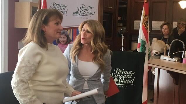 Deux femmes discutent ensemble dans une pièce.