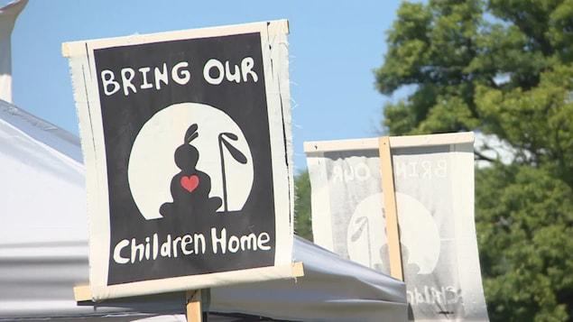 Une affiche sur laquelle on peut lire « rendez-nous nos enfants ».