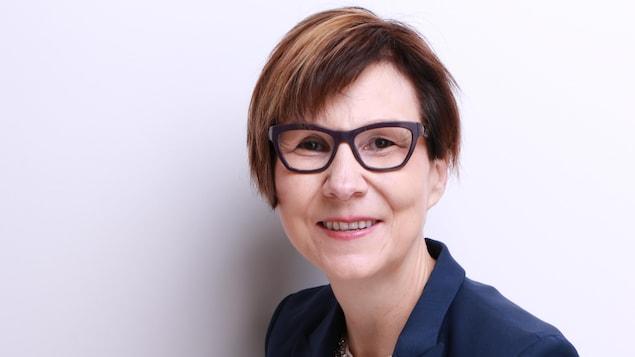 Une femme de face avec des lunettes qui regarde l'objectif