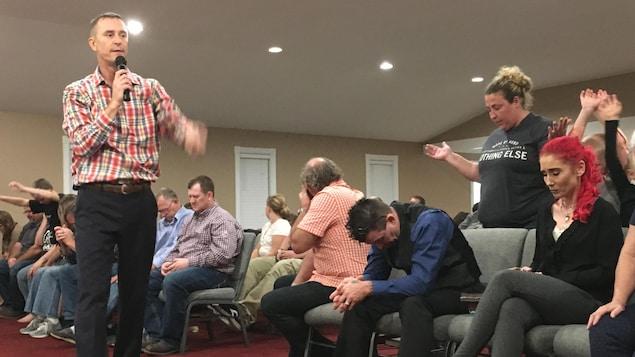 Le pasteur marche, un micro à la main, devant les fidèles qui prient, debout ou assis, avec les yeux fermés.