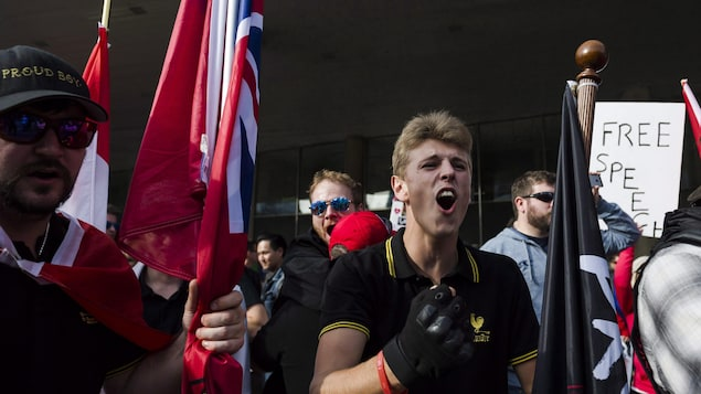 Un joven con una camiseta de los Proud Boys con el puño en alto.