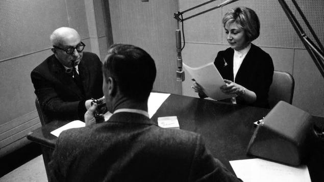 Femme qui tient des feuilles devant un micro et deux hommes dans un studio radio.