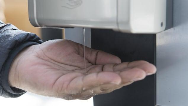 Un homme utilise une solution hydroalcoolique pour se laver les mains.