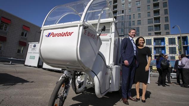 Le PDG de Purolator, John Ferguson  et la mairesse de Montréal, Valérie Plante ,devant un vélo cargo électrique.