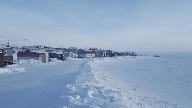 Des maisons sont situées en face de la Baie d'Hudson. Le sol est enneigé.