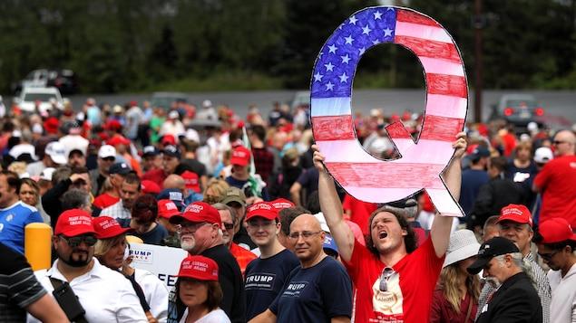 Un homme tient à bout de bras une pancarte en forme de Q à l'effigie du drapeau américain.