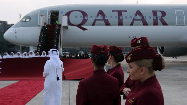 Des membres de l'équipage de Qatar Airways sur le tarmac avec un avion en arrière-plan.