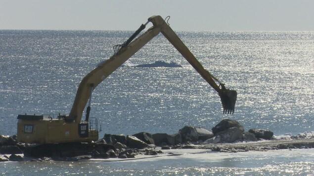 Une grue qui travaille à un enrochement près de la rive.