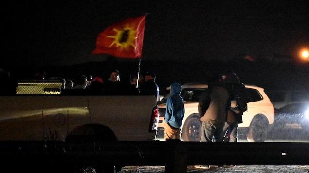 Des personnes dehors tard en soirée près de deux voitures, avec un drapeau.