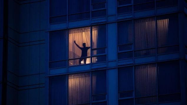 Photographiée de l'extérieur, silhouette d'un homme qui ouvre les rideaux de sa chambre d'hôtel, le soir.