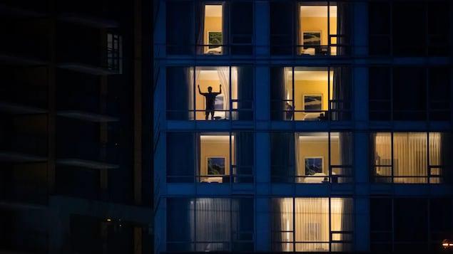 Un homme ouvre les rideaux de sa chambre d'hôtel après le coucher du soleil.