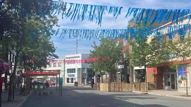 Une rue avec des banderoles accrochées au-dessus, vide de voitures.
