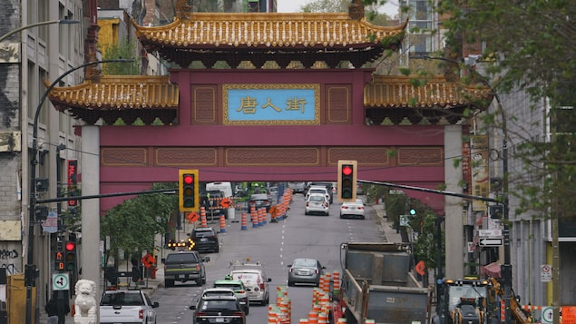 Une vue d'ensemble des portes du quartier chinois de Montréal, sous lesquelles circule un trafic dense parmi des cônes de construction.