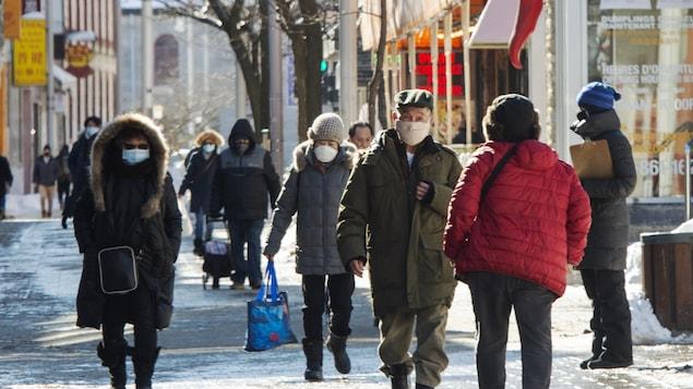 Des gens portant des masques se promènent sur une rue du quartier chinois de Montréal.