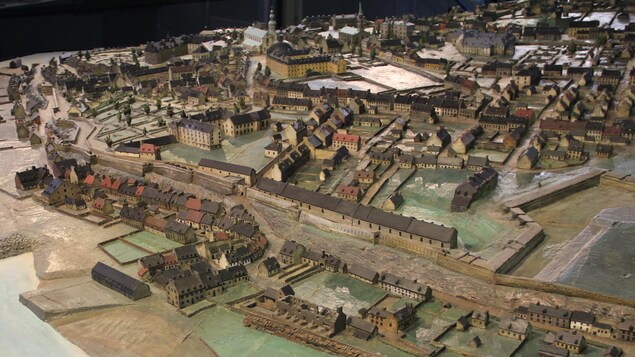 On reconnaît Québec, vue de la rive nord de la rivière Saint-Charles. On voit les casernes, une bonne partie du Vieux-Québec, et une partie de la basse-ville. On devine au loin la place de l'Hôtel de ville. Au premier plan, on peut apercevoir les ruines du palais de l'Intendant, encore visibles à l'époque.