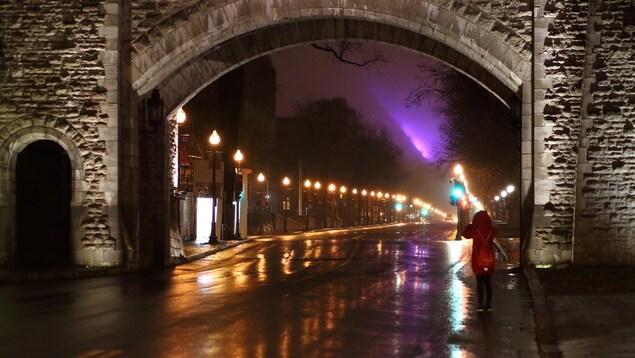 Une touriste photographie la porte St-Louis à Québec, un pluvieux soir d'octobre.