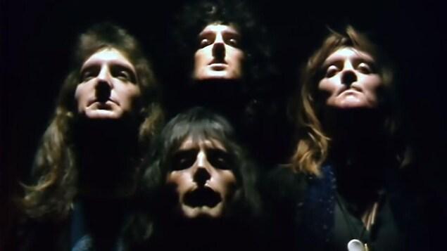 Les quatre musiciens du groupe Queen chantant dans une pièce où des projecteurs éclairent le haut de leur corps et leur visage.