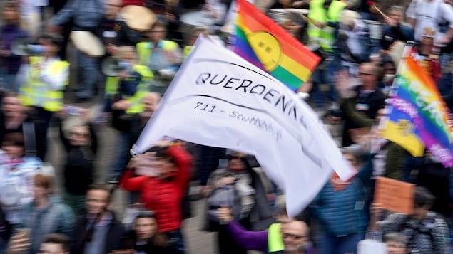Des gens brandissent des drapeaux et des porte-voix lors d'une manifestation en Allemagne.